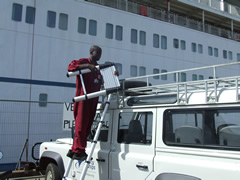 Mercy Ships Land Rover in front of one of Mercy Ships' hospital ships