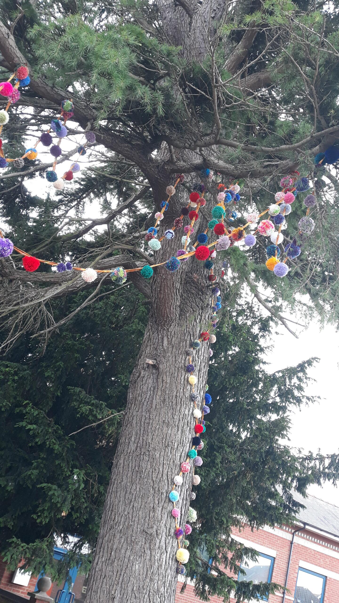 Pompom garland around a tree at Safelincs