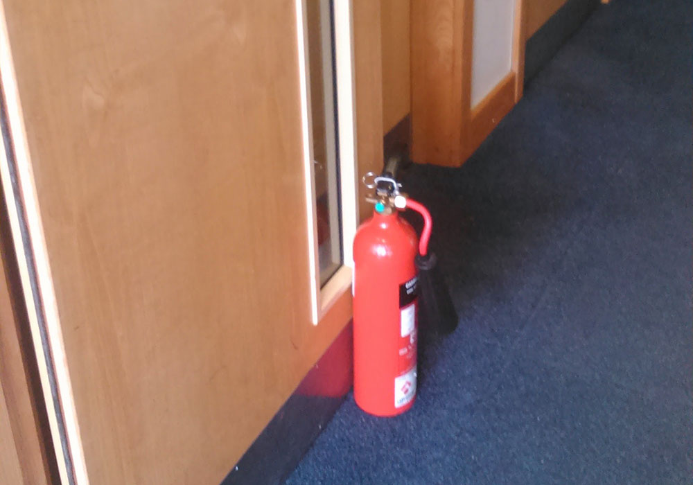 Fire door propped open, not complying with fire door regulations