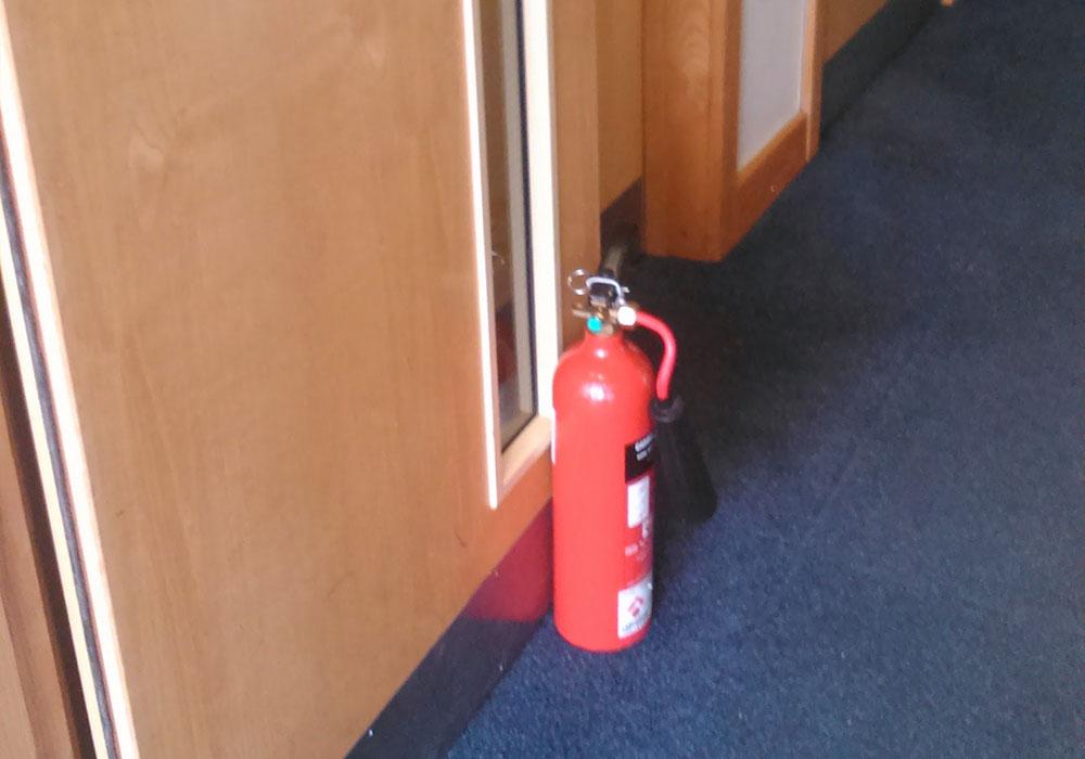 Fire door propped open, not complying with fire door regulations