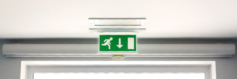Illuminated fire exit sign next to a door