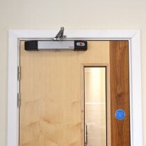 Silver Agrippa door closer on fire door