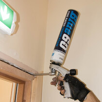 Blue 60 intumescent foam is applied in the gap between fire door frame and wall to stop fire spreading through the gap