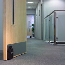 Dorgard Fire Door Retainers Fitted to Door on a Corridor