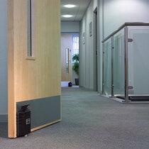 Dorgard Fire Door Retainers Fitted to Door on a Corridor