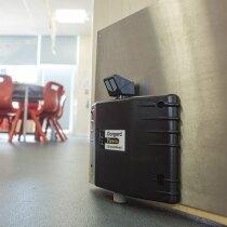 Black Dorgard SmartSound fire door retainer installed on a canteen door