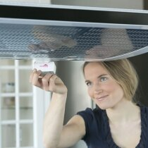 The Innohome Stove Alarm attaches to the cooker hood using magnets